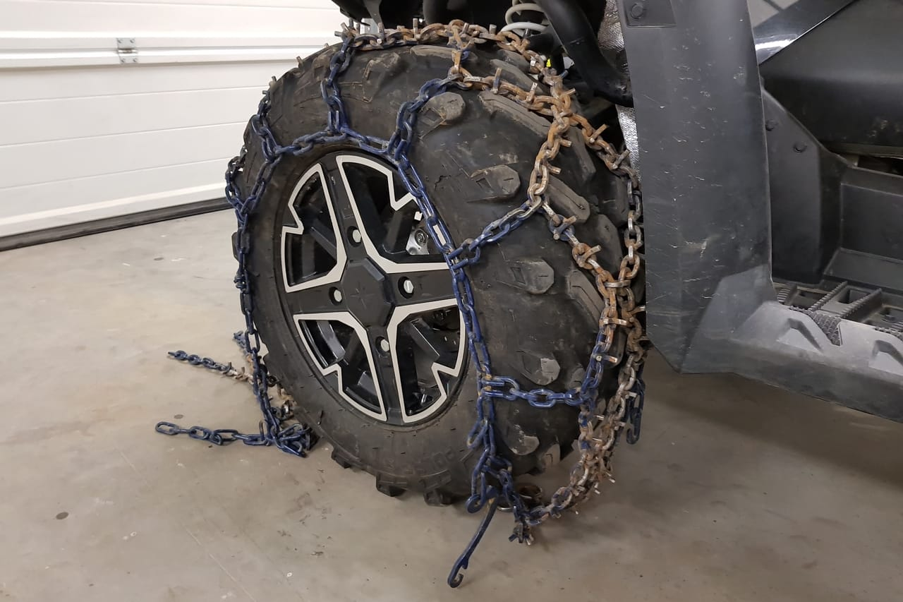 install atv tire chains draped over tire polaris sportsman